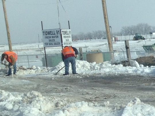 A road crew works to clear snow off railroad tracks