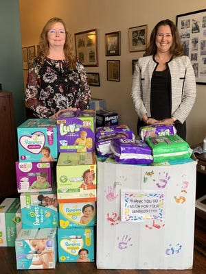 Melodee Campbell, branch office administrator, right, and Edward Jones Financial Advisor Christine Short, left, stand behind the boxes of diapers that were collected in 2020.