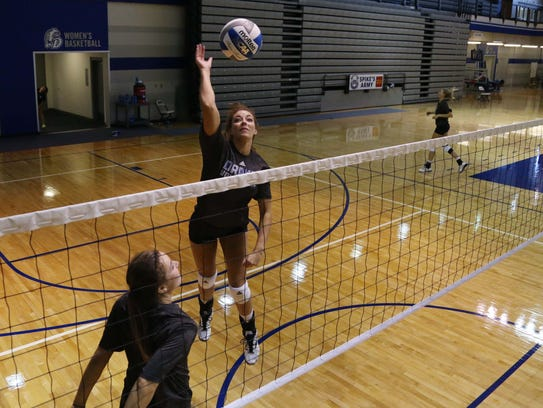 Drake volleyball player  Kyla Inderski, right, leads