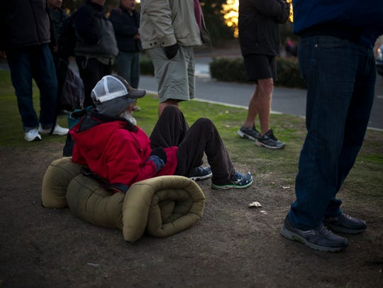 Homeless people wait in line for a free meal Dec. 21