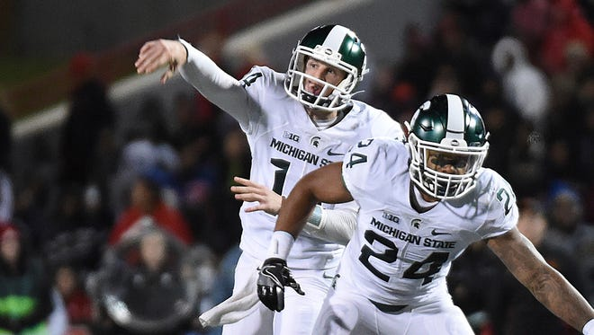 Brian Lewerke throws a pass against Maryland as Gerald Holmes blocks in the first half.