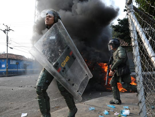 Officers of the Bolivarian National Guard run during