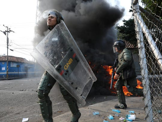 Officers of the Bolivarian National Guard run during clashes in Urena, Venezuela, near the border with Colombia, Saturday, Feb. 23, 2019. Venezuela's National Guard fired tear gas on residents clearing a barricaded border bridge between Venezuela and Colombia on Saturday, heightening tensions over blocked humanitarian aid that opposition leader Juan Guaido has vowed to bring into the country over objections from President Nicolas Maduro.