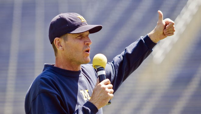 New Michigan football coach Jim Harbaugh says the Wolverines need to be ?better today than we were yesterday.? FILE - In this Aug. 6, 2015, file photo, Michigan head coach Jim Harbaugh greets fans in Michigan Stadium.