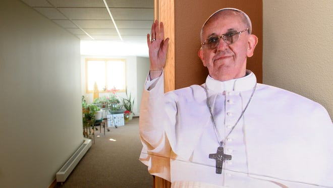 A life sized cutout of Pope Francis waves to passers-by in the hallway of the Poor Clares of Montana monastery.