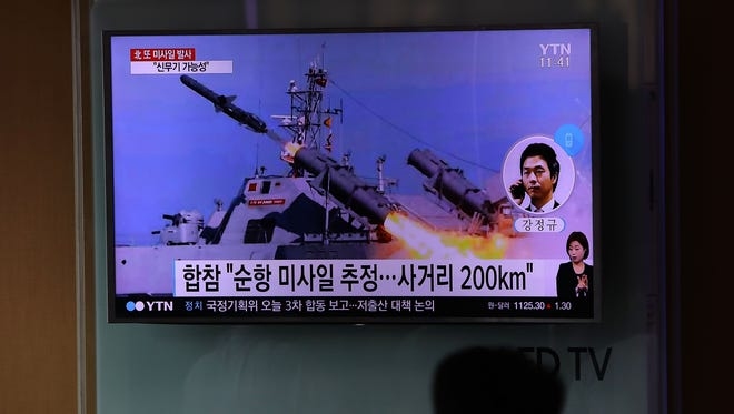 People are pictured watching a television broadcast reporting the North Korean missile launch at the Seoul Railway Station.