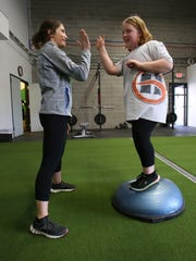 Exercise physiologist Missy Sachs, left, gives Katherine Phinney, 9, a high-five after she performed a balance exercise during a prime class at the Louisville Youth Training Center.  Phinney has been able to halt excessive weight gain with the classes.Mar. 22, 2016