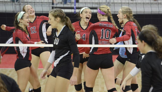 Members of the Newman Catholic girls volleyball team celebrate a point during the WIAA state tournament last November. The Cardinals are among seven local teams that received a No. 1 seed for the postseason this year.