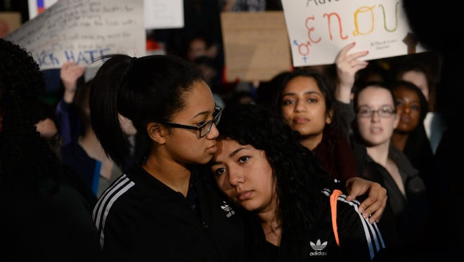 Monica Diaz, right, is comforted by Taylor Vergara-Wright on Thursday at The Rock at Michigan State University during a large gathering to address hate in the nation after the presidential election.