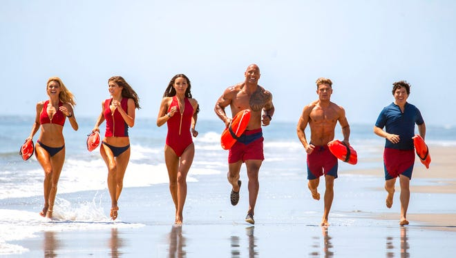 """From left, Kelly Rohrbach as CJ Parker, Alexandra Daddario as Summer, Ilfenesh Hadera as Stephanie Holden, Dwayne Johnson as Mitch Buchannon, Zac Efron as Matt Brody and Jon Bass as Ronnie in """"Baywatch."""" The movie opens Wednesday at Regal West Manchester Stadium 13, Frank Theatres Queensgate Stadium 13 and R/C Hanover Movies."""