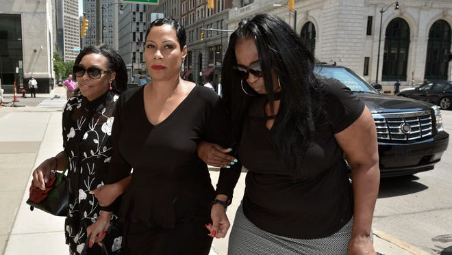 Monica Morgan-Holiefield, center, is escorted by two unidentified women as she enters the federal courthouse in downtown Detroit Friday  for her sentencing hearing.