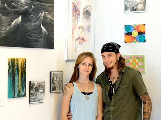 The Rooted Artist Collective co-owners Jessica Flynn and Dustin Nispel pose in their shop Monday, Sept. 14, 2015. The couple is raising funds to attend the International Poetry Festival in Macedonia. With equipment borrowed for White Rose Community Television, they are creating a documentary of their travels. Bill Kalina - bkalina@yorkdispatch.com