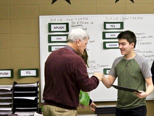 Paul Aleckson congratulates a student.