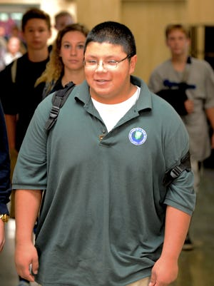 Notre Dame Academy sophomore David Torres heads to choir class at the school last month.