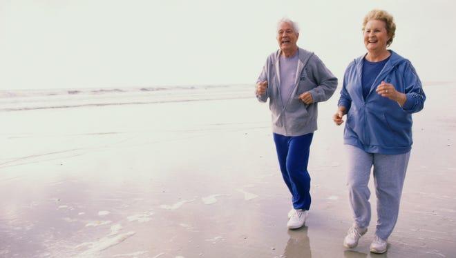Elderly couple jogging on a beach