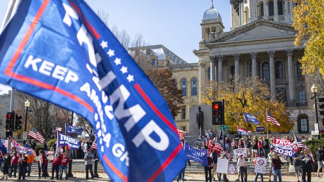 """Supporters of President Donald Trump hold up signs with """"Stop the Steal"""" during a rally in front of the Abraham Lincoln statue at the Illinois State Capitol, Saturday, November 7, 2020, in Springfield, Ill."""