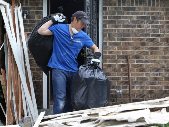 Terry Purchal carries garbage bags full of flood-damaged