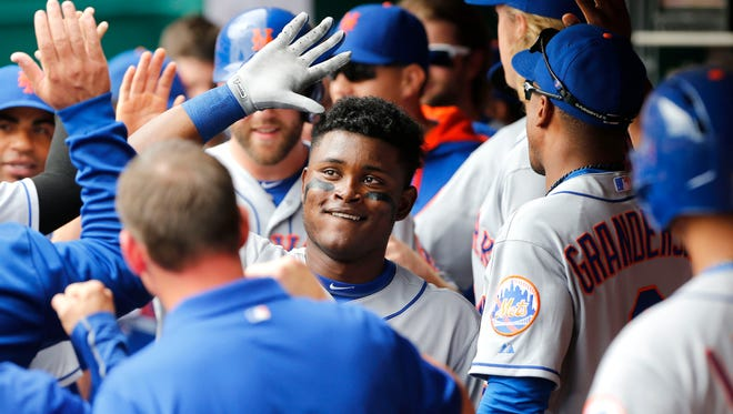 New York Mets second baseman Dilson Herrera (16) celebrates with teammates in the dugout after hitting a two-run home run in the second inning of a baseball game against the Cincinnati Reds, Sunday, Sept. 27, 2015, in Cincinnati.