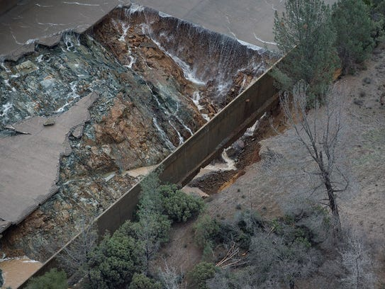 Water spills into a gaping hole at the Oroville Dam
