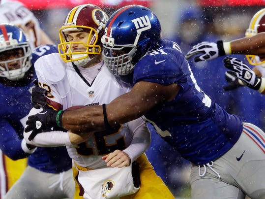 FILE - In this Dec. 29, 2013, file photo, New York Giants defensive end Justin Tuck, right, sacks Washington Redskins' Kirk Cousins (12) during the first half of an NFL football game in East Rutherford, N.J. Tuck signed with the Oakland Raiders. (AP Photo/Julio Cortez, File)