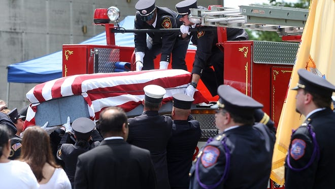 Hinal K. Patel's casket is lowered from a North Stelton fire truck, Monday, July 27, 2015, at the Franklin Memorial Park in North Brunswick, NJ.  Patel, age 22, was killed when her Spotswood ambulance was involved in a motor vehicle accident in East Brunswick.
