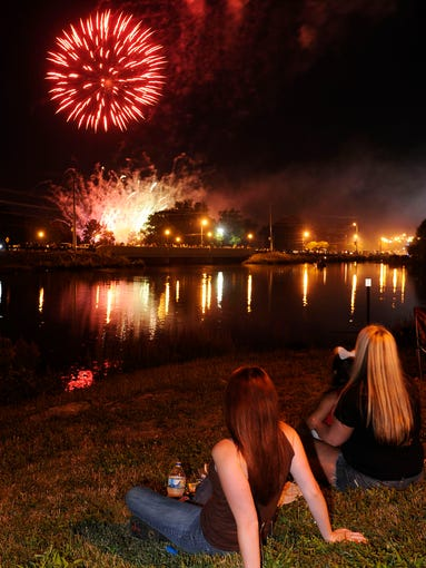 Dianna Biggs, near, sits with Alannah Wombles, 3, and Nicole Wombles, right, during the fireworks display at the Freedom Festival at Drakes Creek Park Thursday, July 3, 2014 in Hendersonville, TN.