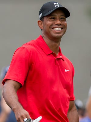 Tiger Woods smiles at the third tee during the final round of the Wyndham Championship golf tournament.