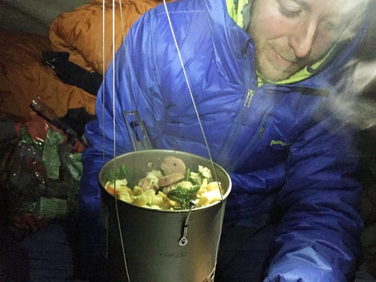 In this Dec. 29, 2014 photo by Kevin Jorgeson, Tommy Caldwell eats dinner during what has been called the hardest rock climb in the world: a free climb of a El Capitan, the largest monolith of granite in the world, a half-mile section of exposed granite in California's Yosemite National Park. (AP Photo/Kevin Jorgeson, elcapreport)