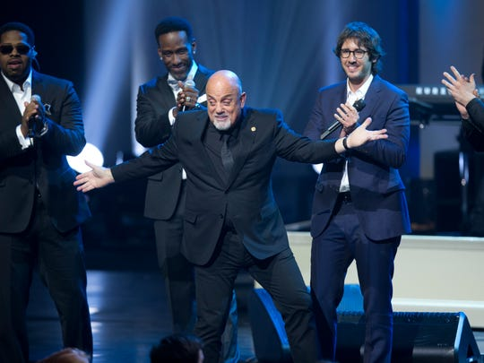 Billy Joel takes in the applause during a tribute concert in his honor after he received the Library of Congress Gershwin Prize for Popular Song in Washington on Nov. 19, 2014. On stage with him are (from left) Nathan Morris and Shawn Stockman of Boyz II Men, Josh Groban, and Gavin DeGraw.