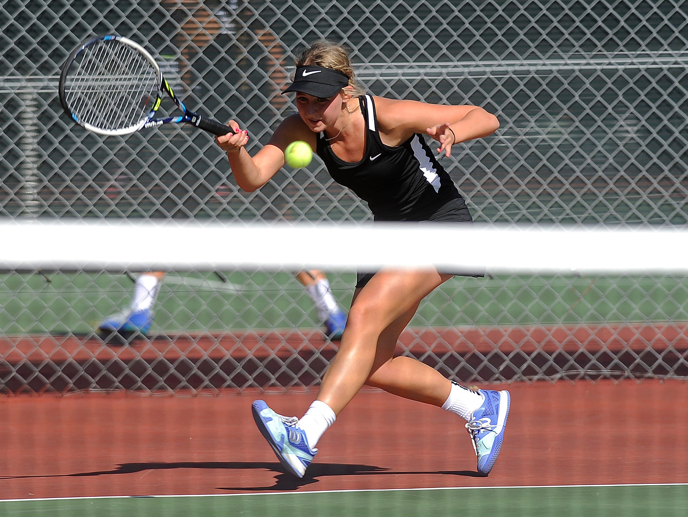 St. Thomas More's Madison Fenske returns the ball to O'Gorman's Danielle Sebata during the singles championship finals of the SD high school girls state tennis tournament at McKennan Park in Sioux Falls, SD; Saturday, Oct. 10, 2015.