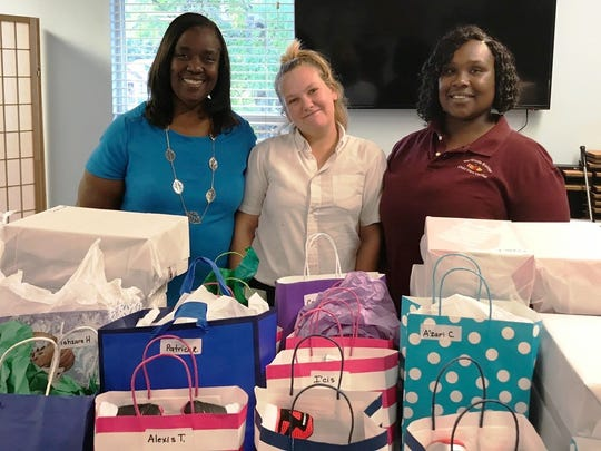 Thelma Washington, Megan McLaughlin and Erica Gray gift wrap the 120 pairs of shoes to be donated to the children in the East Stuart Youth Initiative,