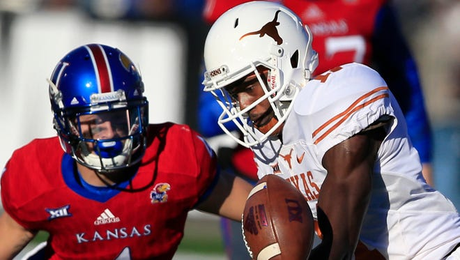 Texas wide receiver Jacorey Warrick (11) catches a pass while he is covered by Kansas safety Shaquille Richmond (4) during the first half of their game in Lawrencde, Kan.
