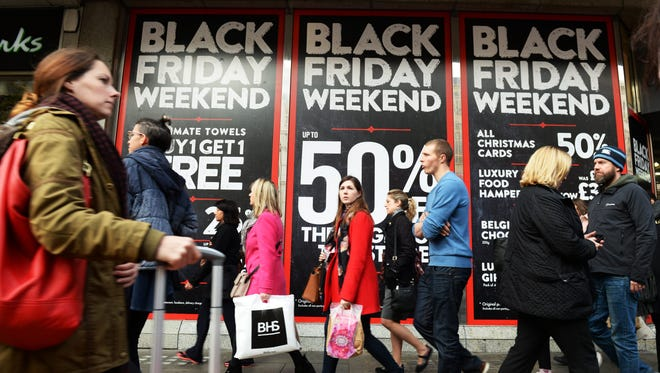Shoppers pass a store offering Black Friday sales on Oxford Street in London on Nov. 28.
