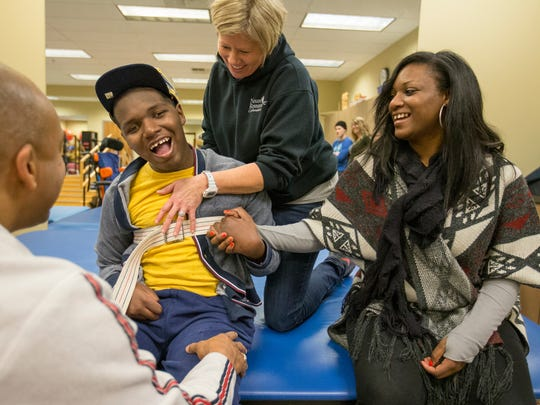 DeAndre Knox sits with his mother Deandra Yates, as he is helped by Kathy Mileur (middle), Murphysboro, Ill., and Will Bollinger, Carbondale,  who work at Neuro Restorative, Carbondale, Ill., Thursday, January 21, 2016. Knox was shot in 2014, and has a long road of physical therapy ahead.