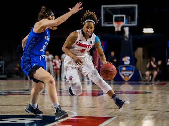 Liberty's Tatyana Crowder (4) drives around UNC Asheville's Ali Trani (32) during the first half of the Big South Conference women's NCAA basketball championship game in Lynchburg,Va., Sunday, March 11, 2018. (AP Photo/Lee Luther Jr.)