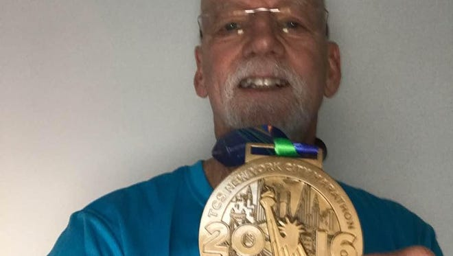 New Paltz resident Dennis Moore shows off his medal from the New York City Marathon.