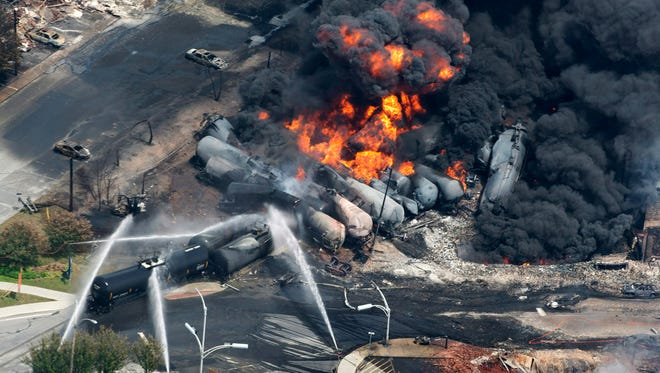In this July 6, 2013 file photo, smoke rises from railway cars carrying crude oil after derailing in downtown Lac Megantic, Quebec. American Petroleum Institute President Jack Gerard said Tuesday that the oil and railroad industries are urging federal regulators to allow them as long as seven years to retrofit existing tank cars that transport highly volatile crude oil.