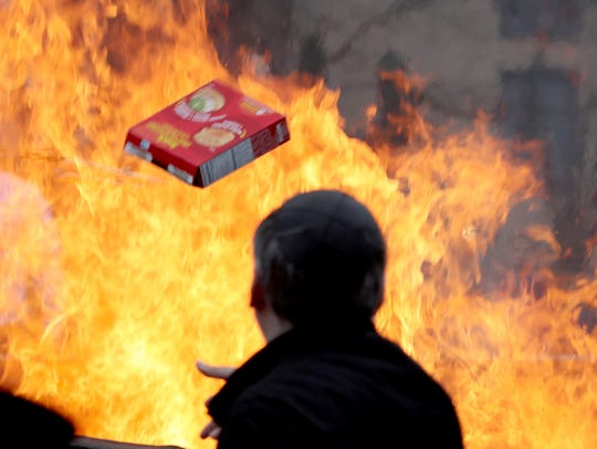 Orthodox Jews throw bread products into a fire at the