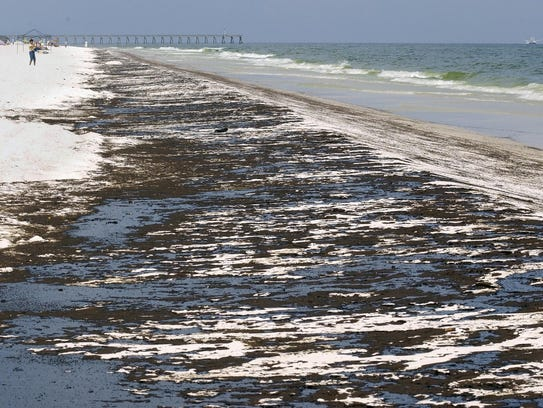 Mats of oil from the Deepwater Horizon oil spill washed ashore along Pensacola Beach on June 23, 2010.