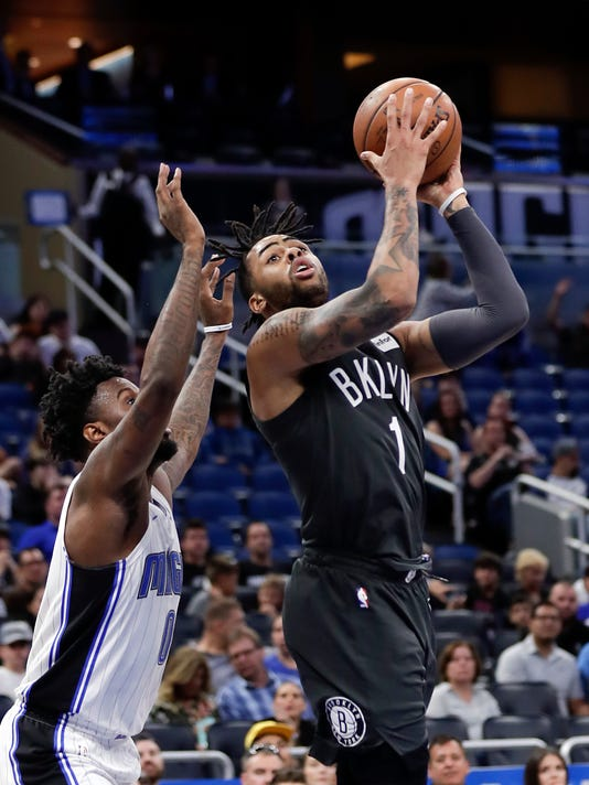 Brooklyn Nets' D'Angelo Russell (1) goes up for a shot against Orlando Magic's Jamel Artis, left, during the second half of an NBA basketball game, Wednesday, March 28, 2018, in Orlando, Fla. (AP Photo/John Raoux)
