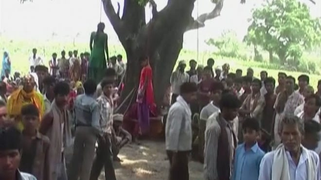 Villagers gather around the bodies of two teenage sisters hanging from a tree in Katra village, India, on May 28.