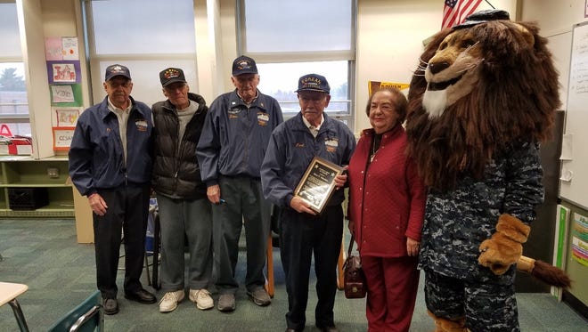 (From left) James Halferty, Michael Pedulla, Steve Tobolski and Carl Biletta, members of the Korean War Veterans of Vineland, present Barbara Maurizio, wife of the late Salve Maurizio, with a plaque to honor Salve for his commitment to the school, community and veterans, as Sgt. Roary, the school mascot, looks on. Veterans Phil Petalino and John Viola are missing from the picture.