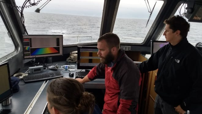 The survey team is reviewing data collected by a multibeam echo sounder. Left to right: Jen Kraus (NCCOS), John Bright (Thunder Bay National Marine Sanctuary), and Will Sautter (NCCOS).