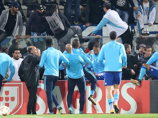 Marseille's Patrice Evra, center, back to camera is dragged away by his teammates during a scuffle with Marseille supporters who trespassed onto the field before the Europa League group I soccer match between Vitoria SC and Olympique de Marseille at the D. Afonso Henriques stadium in Guimaraes, Portugal. UEFA has suspended Marseille defender Patrice Evra until June 2018 for kicking one his own team's fans before a Europa League game. (AP Photo/Luis Vieira, File)