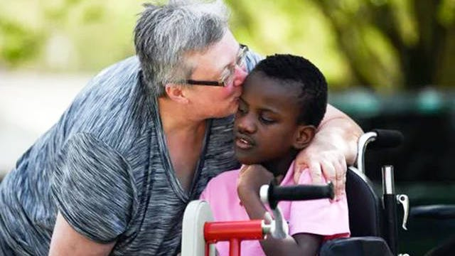 Tori Wentz kisses her son Ricky, 11, outside their West Knoxville home on March 26.