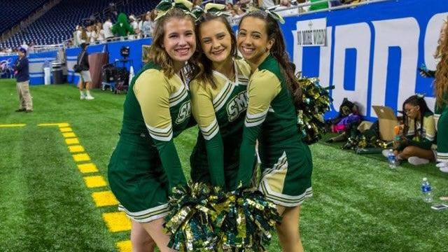 "St. Mary Catholic Central's Madalyn Poupard (right) and Kristen Meiser (center) pose for a photo with teammate Delaney Puckett during SMCC's state championship victory at Ford Field in November. ""Having the opportunity to go to Ford Field is something I will never forget. It was definitely my favorite memory from senior year,"" Poupard said. ""Walking on that field was just a feeling I'll never be able to quite put into words. It was so phenomenal. To be able to cheer on a field like that is an unforgettable experience."""