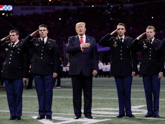 President Donald Trump sings the national anthem before the NCAA college football playoff championship game between Georgia and the AlabamaMonday, Jan. 8, 2018, in Atlanta.