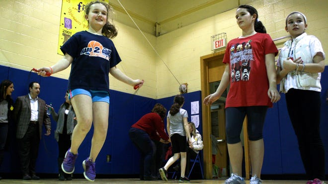 Madeline Weld, 10, left, jumps rope at French Road Elementary School's annual Jump Rope for Heart fundraiser while friends look on.