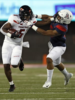 Texas Tech's Armand Shyne stiff-arms Arizona's Scottie Young Jr. during the teams' 2019 game. Tech was scheduled to play Pac-12 school Arizona State in 2020, but that game was canceled Friday as Pac-12 officials scuttled all nonconference games this year.