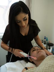 Glitz esthetician student Tracey Rivera, left, performs a high frequency treatment on student Kacey Almanza. High frequency treatment uses an electrical current to kill bacteria and to keep it from spreading on the face.